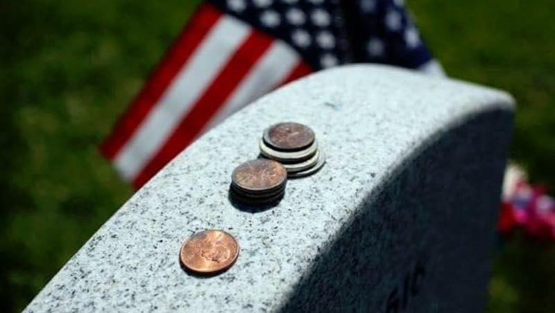 What do coins on a headstone mean